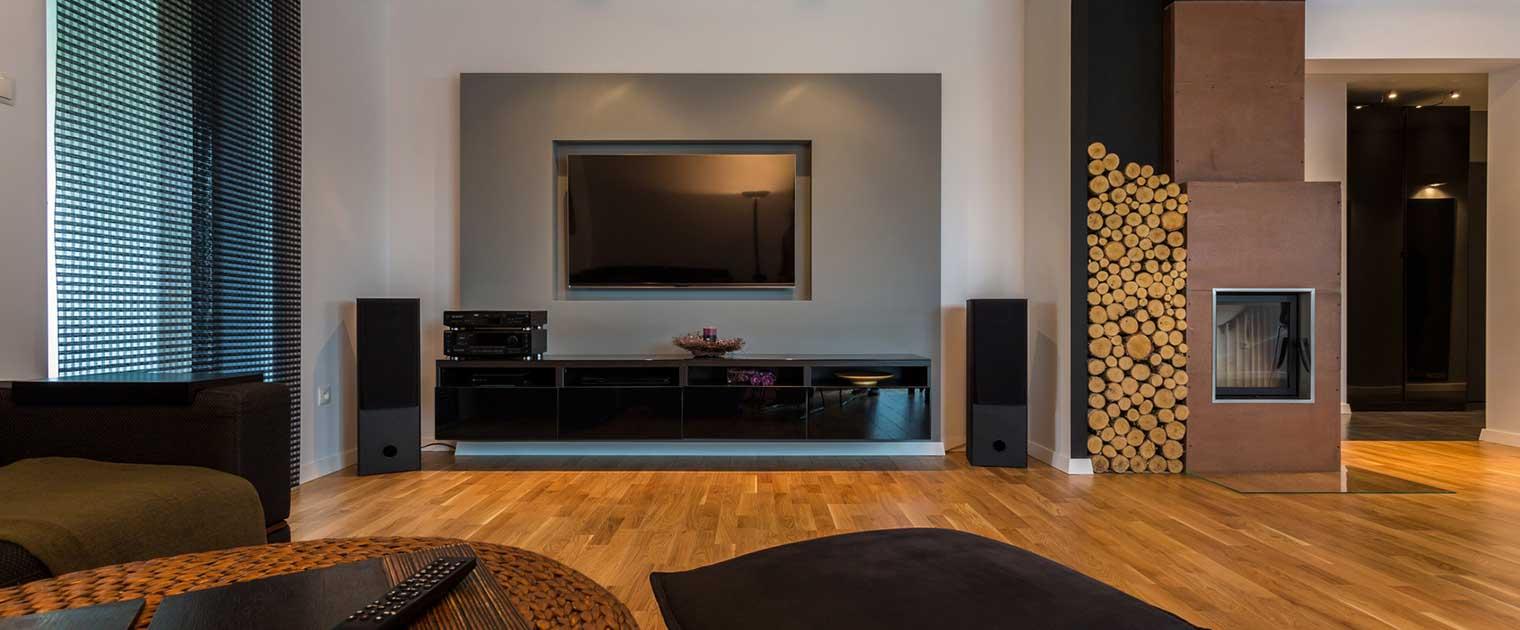 Ein modernes Wohnzimmer mit Fernseher und Kachelofen